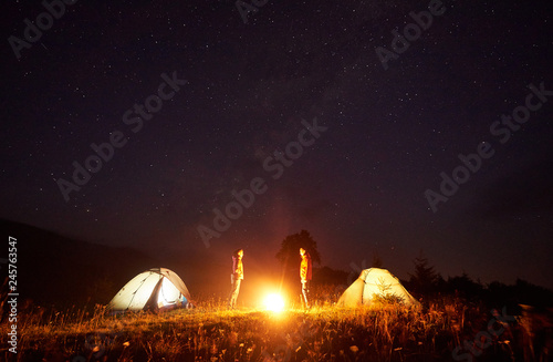 Night camping. Bright bonfire burning between two tourists, boy and girl standing opposite each other in front of illuminated tents under beautiful dark starry sky on distant hills background.