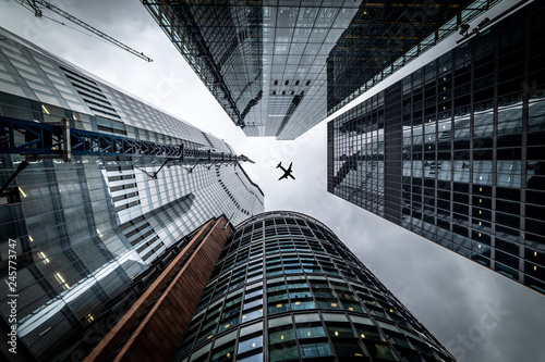 Silhouette of a jet plane flying low over Three different kind of architecture with commercial office buildings exterior in London