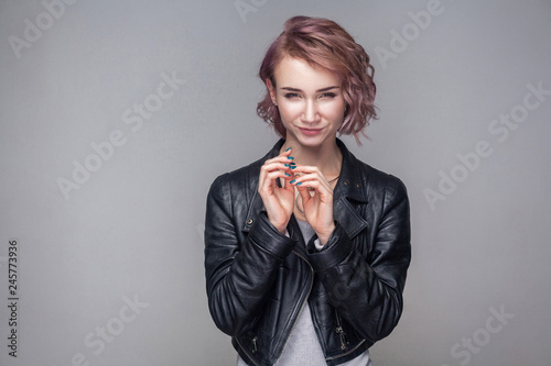 Portrait of cheater beautiful girl with short hairstyle, makeup in casual style black leather jacket standing with cunning idea and looking at camera Wallpaper Mural