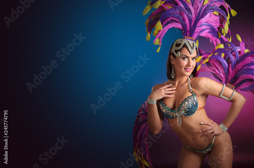 Fototapeta Attractive female cabaret dancer in costume with blue and purple feathers