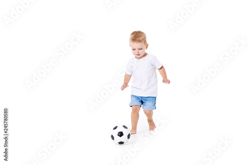 Photo Little cute kid baby boy 3 years old, football fan in white t-shirt playing with soccer ball isolated on white background