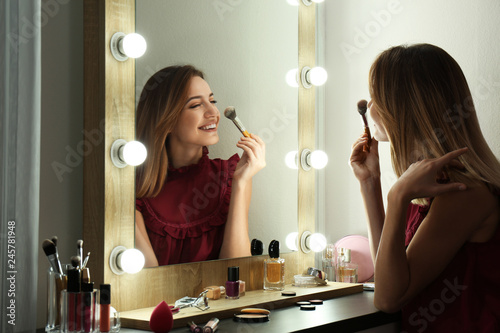 Fotografie, Obraz  Woman applying makeup near mirror with light bulbs in dressing room