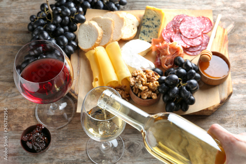 Fotografía  Woman pouring white wine into glass on table with delicious food, closeup