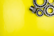 canvas print picture - Ball bearing lying on a yellow background with copy space on the left side. Flat view from above.