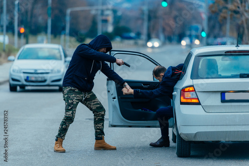 Fotografía  The car thief is pulling the car owner out of his car and trying to get the car while pointing a loaded gun at the drivers head