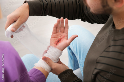 Young man applying bandage on woman's injured hand at home, closeup. First aid