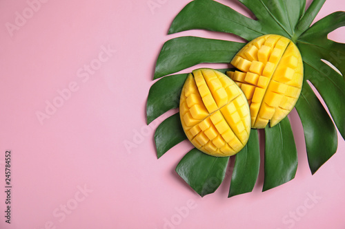 Staande foto Roze Flat lay composition with cut mango, monstera leaf and space for text on color background
