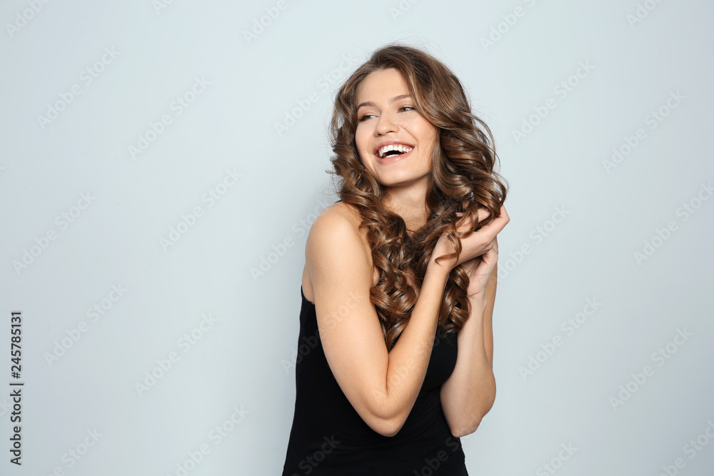 Fototapeta Portrait of beautiful young woman with shiny wavy hair on color background