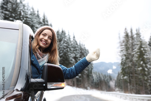 Young woman driving car and looking out of window on road. Winter vacation