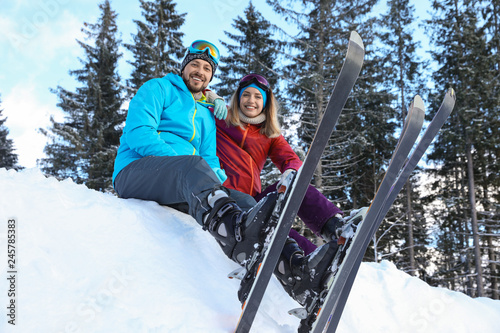 Spoed Foto op Canvas Wintersporten Happy couple with ski equipment sitting on snowdrift outdoors. Winter vacation