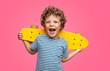 Leinwandbild Motiv Happy curly boy laughing and holding skateboard