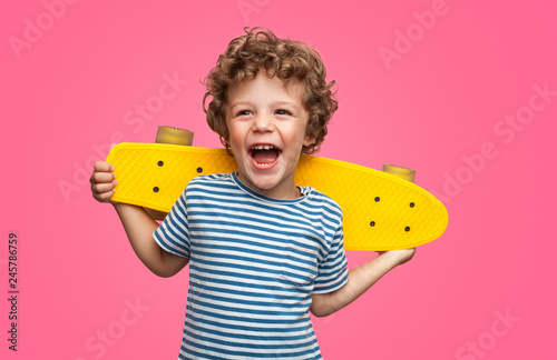Happy curly boy laughing and holding skateboard