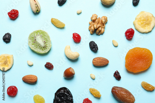 Flat lay composition of different dried fruits and nuts on color background