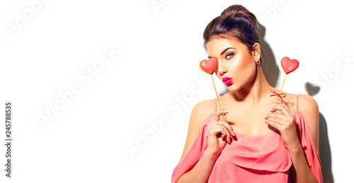 Valentines Day. Beauty joyful young fashion model girl with Valentine heart shaped cookies in her hands isolated on white