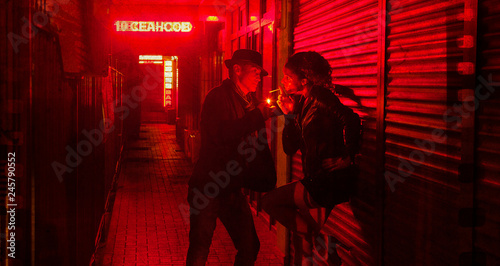 man is lighting a cigarette for a woman at  wall in a street of red lanterns at Fototapet