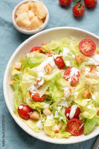 Fotografía  Caesar salad with sauce on plate, top view, closeup