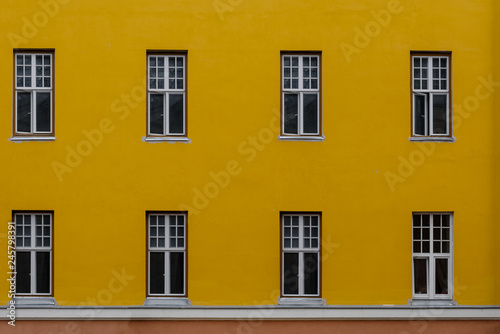 Fotografía  Closeup photo of bright yellow building with eight windows