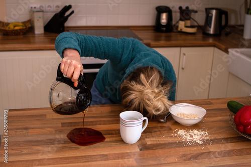 Fototapeta Müde Frau mit Kopf auf Tisch verschüttet ihren Kaffee