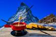 canvas print picture - Fondue cheese, swiss winter ski holidays break for lunch, mountain view Matterhorn in Zermatt, Switzerland.