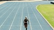 Fit woman running on racetrack during training session. Female runner practicing on athletics race track. Aerial moving shot.