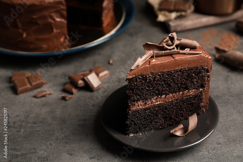 Plate with slice of tasty homemade chocolate cake on grey table. Space for text