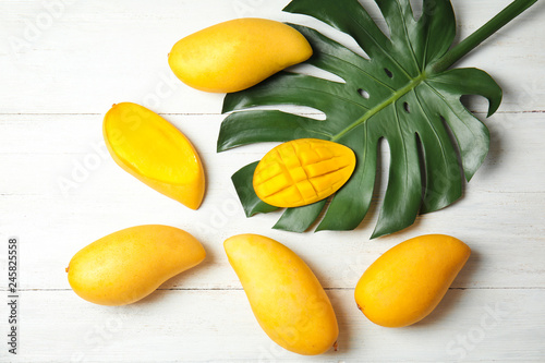 Flat lay composition with mango and tropical leaf on wooden background