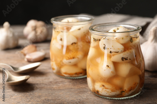 In de dag Aromatische Preserved garlic in glass jars on wooden table, closeup. Space for text