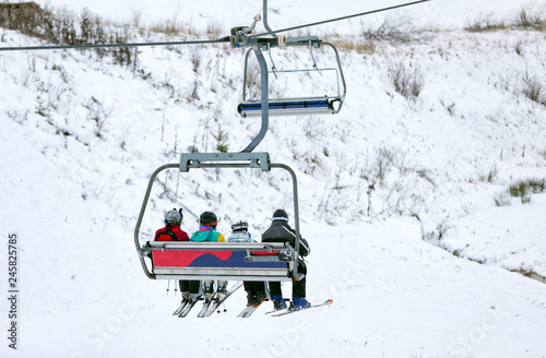 Chairlift with people at ski resort. Winter vacation