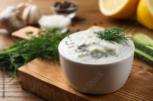 Cucumber sauce with ingredients on wooden background, space for text. Traditional Tzatziki