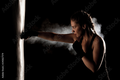Fototapeta kick fighter girl punching a boxing bag
