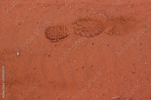 trekking shoes foot print on vivid orange desert sand