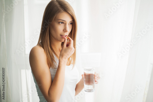 Obraz Happy smiling positive woman eating the pill and holding the glass of water in the hand, in her home - fototapety do salonu