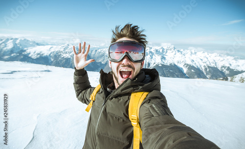 Fotomural  Portrait of an andsome man is taking a selfie in the snow on a mountain at winte