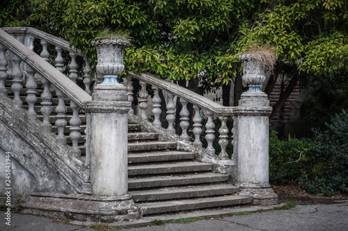 Ancient staircase with stone balusters against the background of green vegetation Canvas Print