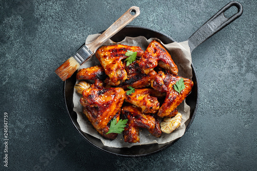 Photo  Baked chicken wings in barbecue sauce with sesame seeds and parsley in a cast iron pan on a dark concrete table
