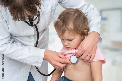 Fotografiet  Pediatrician doctor examining a little girl by stethoscope