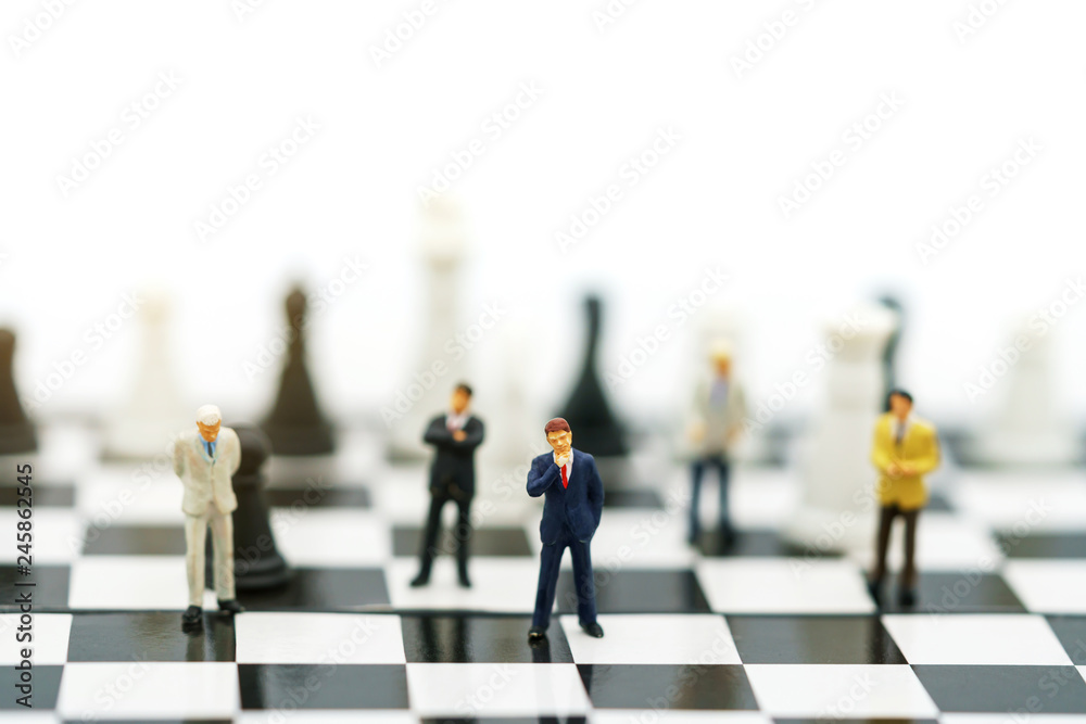 Fotografia Miniature people: Businessman handshake to business success on chessboard