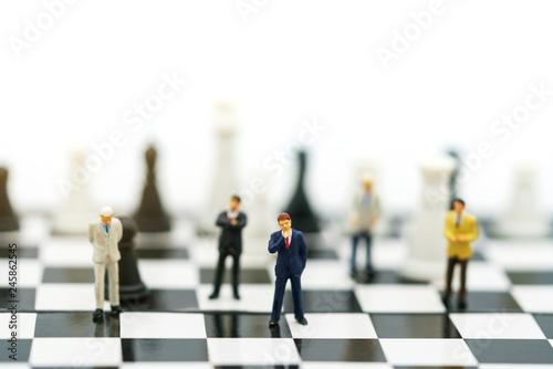 Miniature people: Businessman handshake to business success on chessboard Fototapeta