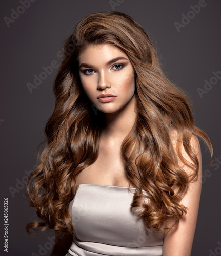 Young brown-haired woman with long curly hair. Wall mural