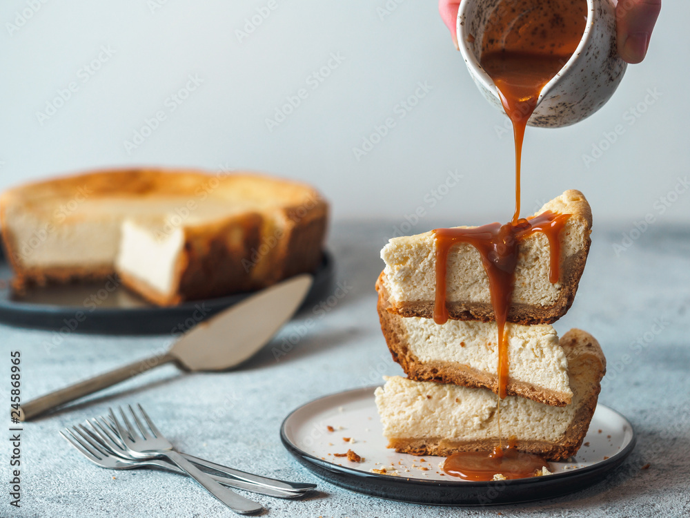 Fototapety, obrazy: Caramel pouring on stack of three cheesekace pieces. Cheesecake with caramel on gray cement background. Copy space for text.