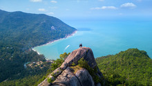 Man And Woman Standing On Cliff's Edge And Looking Into A Sand Beach Of Koh Phangan Island,Thailand