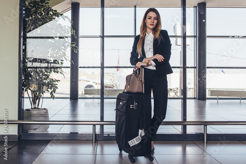 Obraz na plátně Beautiful airhostess standing in her uniform with her bags ready for a flight