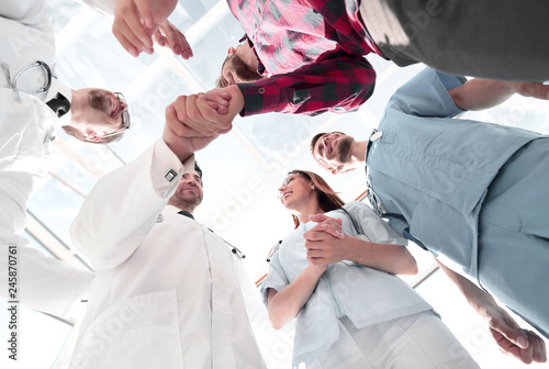 Doctors greet a colleague in a team with a handshake
