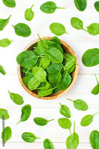 Fresh green spinach leaves on wooden bowl on white wooden rustic background top view copy space. Baby young spinach leaves, Ingredient for salad, healthy food, diet. Nutrition concept.