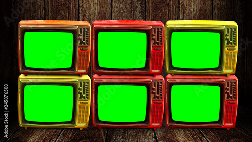 Group of retro television with green screen at wooden floor and wall background