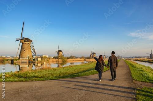 Foto auf Leinwand Rotterdam Rotterdam Netherlands, Love couple walking with Dutch Windmill at Kinderdijk Village