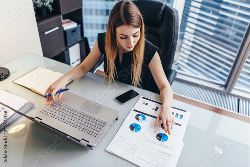 Female businesswoman readind financial report analyzing statistics pointing at p Canvas Print