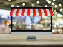 Desktop Modern Computer Monitor With Online Shopping Store Graphic And Open Sign On Wooden Table Over Blur Light And Shadow Of Shopping Mall, Business Internet Shop Online Concept