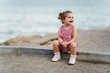 toddler girl sitting on concrete sidewalk.Natural light. Selective focus.