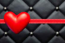 Red Heart And Ribbon On Black Quilted Leather